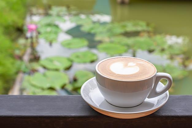 Piatto bianco con tazze di caffè con il trucco a forma di cuore sui balconi in ferro