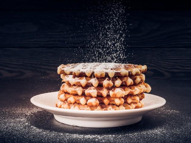 Piatto bianco con waffle belgi fatti in casa, in cima a setacciatura di zucchero a velo nero, snack molto gustoso. zucchero sul vecchio tavolo di legno. stile rustico scuro