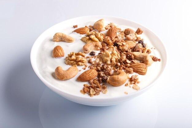 Piatto bianco con yogurt greco, muesli, mandorle, anacardi, noci