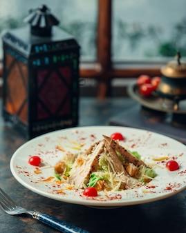 Piatto bianco di caesar salad decoratd con pomodorini