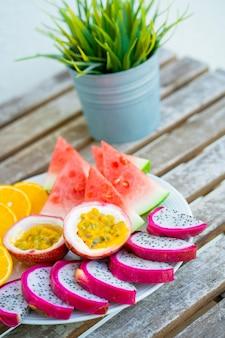 Piatto bianco di frutta a fette. frutta e vitamine fresche. frutta estiva colorata di natura morta.