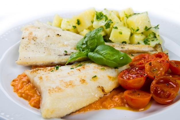 Piatto bianco di merluzzo nero fresco con patate e salsa di pomodori