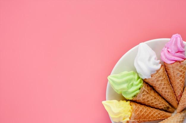Piatto bianco di vari di cono gelato su sfondo rosa per desse dolce e rinfrescante