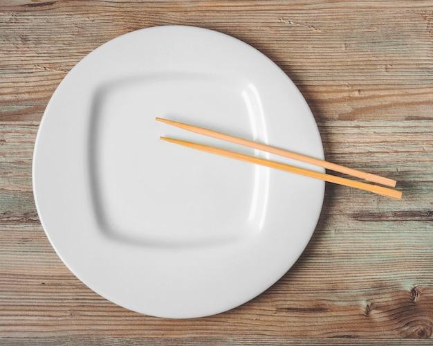 Piatto bianco e bacchette per sushi