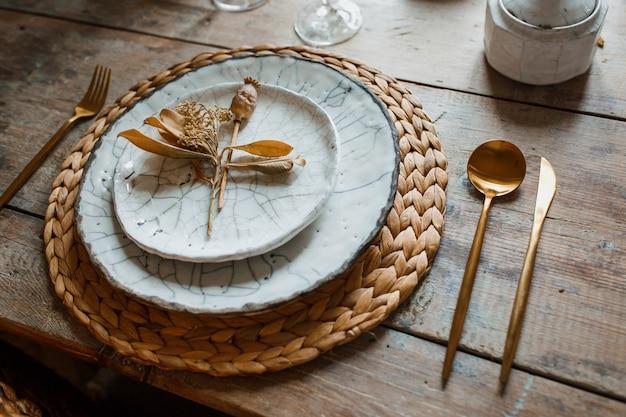 Piatto bianco e forchetta d'oro con un cucchiaio
