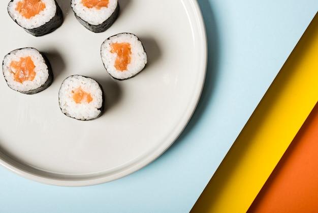 Piatto bianco minimalista con involtini di sushi