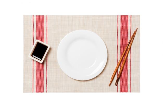 Piatto bianco rotondo vuoto con le bacchette per sushi e salsa di soia sulla stuoia di sushi