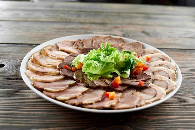 Piatto bianco su un tavolo di legno pieno di assortimento di carne ripiena, decorato con foglie e pezzi di lattuga fresca. delizioso antipasto al ristorante.