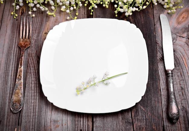 Piatto bianco vuoto con posate in ferro