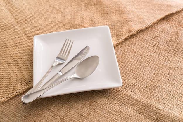 Piatto bianco vuoto e cucchiaio, forchetta, coltello