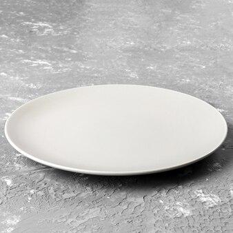 Piatto bianco vuoto su superficie ruvida