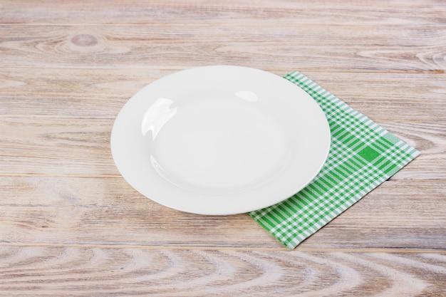 Piatto bianco vuoto sulla tavola di legno