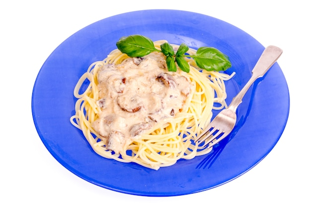 Piatto blu con salsa di spaghetti e funghi.