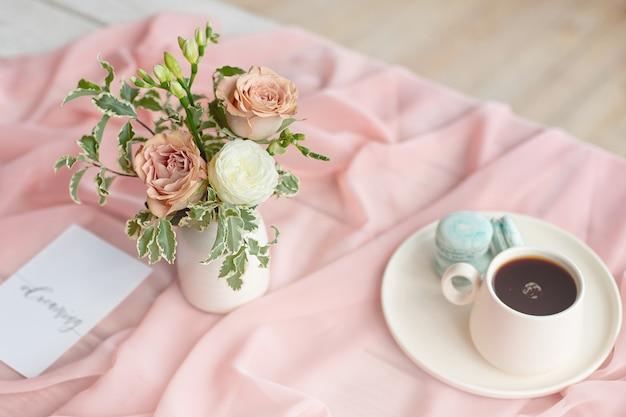 Piatto blu del maccherone francese sul rosa e sulla tazza di caffè che stanno su una tavola di legno con il vaso bianco della tovaglia rosa con le rose e le verdure dei fiori.