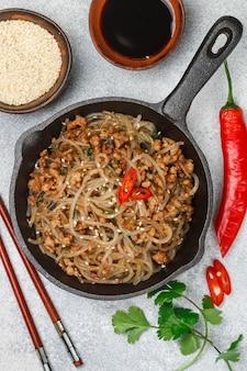 Piatto cinese di tagliatelle in vetro di amido con salsa di soia di carne, zenzero, sesamo, coriandolo, peperoncino