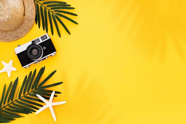 Piatto con accessori da viaggio: foglia di palma tropicale, fotocamera retrò, cappello da sole, stelle marine su sfondo giallo