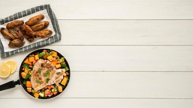 Piatto con ali di pollo e padella di verdure sulla scrivania in legno