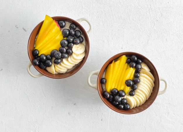 Piatto con farina d'avena e mango, mirtillo, banana su una vista superiore bianca. tavolo per la colazione gustoso e salutare