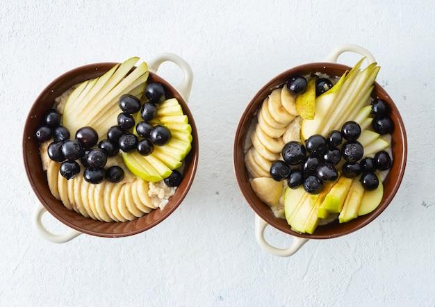 Piatto con farina d'avena e pera, mela, mirtillo, banana su una vista superiore bianca. tavolo per la colazione
