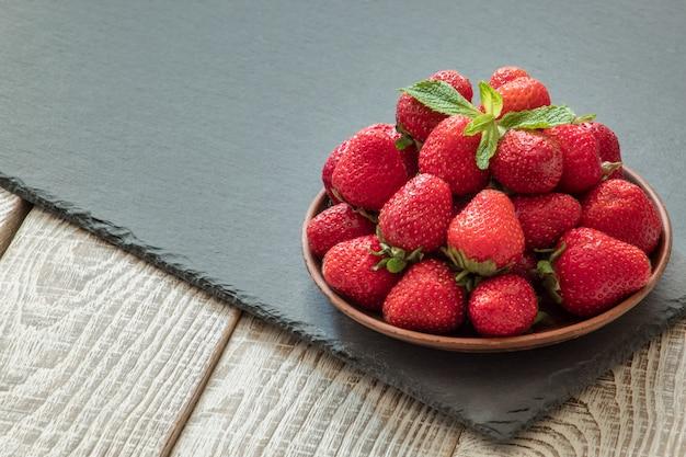 Piatto con fragole fresche succose sul tavolo di legno