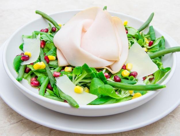 Piatto con insalata fresca e fette di prosciutto
