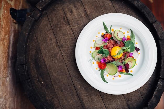 Piatto con insalata fresca su barile di legno