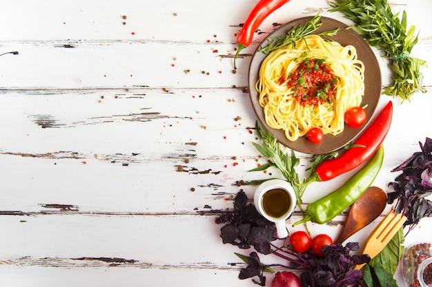 Piatto con pasta. ciliegia, peperoncino, pomodoro, basilico, spezie, dragoncello, cipolla