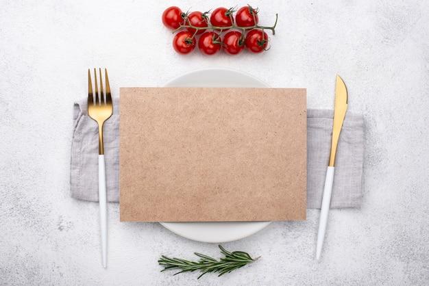 Piatto con posate e pomodori sul tavolo