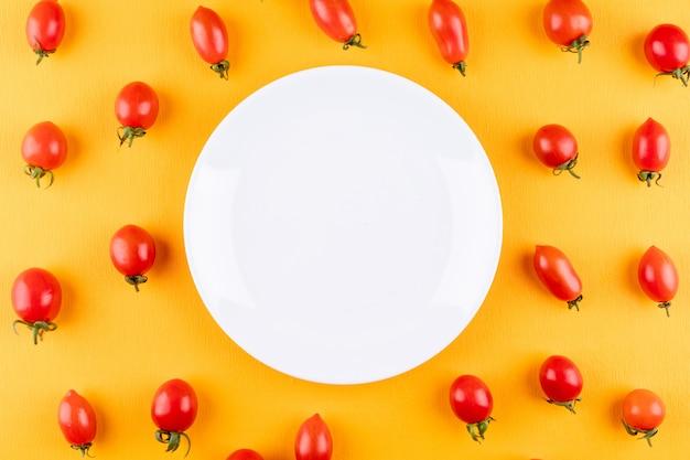 Piatto con spazio di copia circondato da pomodorini freschi rossi su giallo