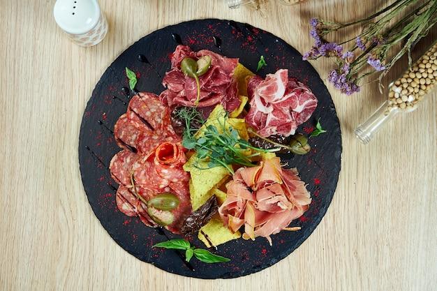 Piatto con tapas antipasti. patatine jamon, salame, prosciutto e nacho su una tavola di ardesia nera. avvicinamento. vista dall'alto cibo piatto laico. piatto di antipasti