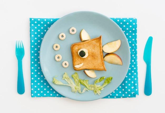 Piatto con toast a forma di pesce con mela sulla scrivania