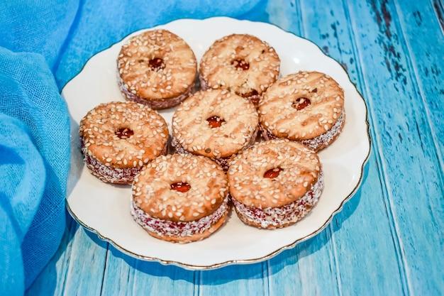 Piatto con un biscotto di pasta frolla su un fondo di legno blu.