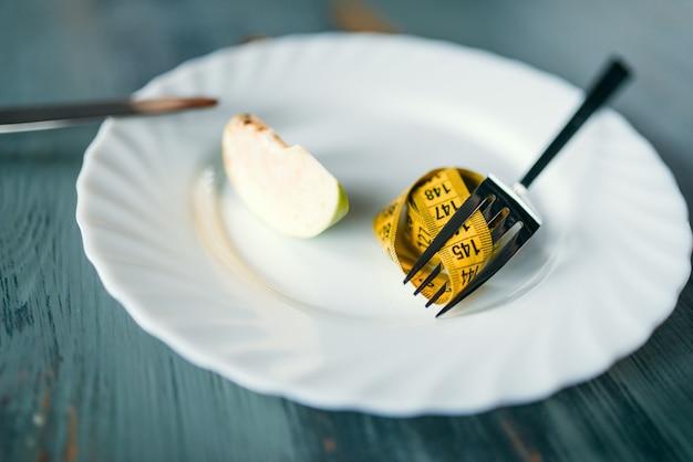 Piatto con una fetta di mela e primo piano del nastro di misurazione. concetto di dieta dimagrante