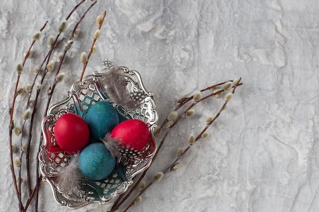 Piatto con uova dipinte e salice su uno sfondo grigio - sfondo di pasqua