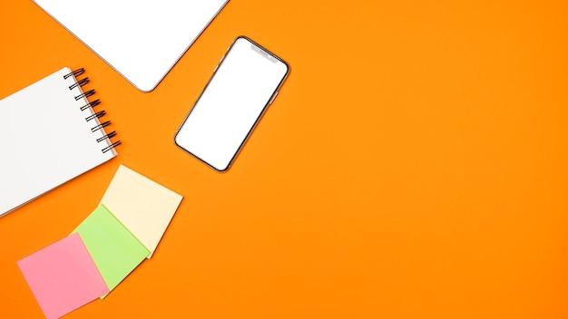 Piatto concetto di area di lavoro laici con sfondo arancione