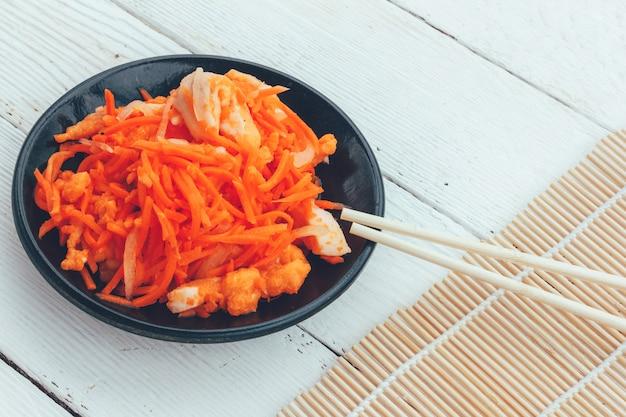 Piatto coreano di carote e pesce rosso e bacchette su fondo di legno bianco
