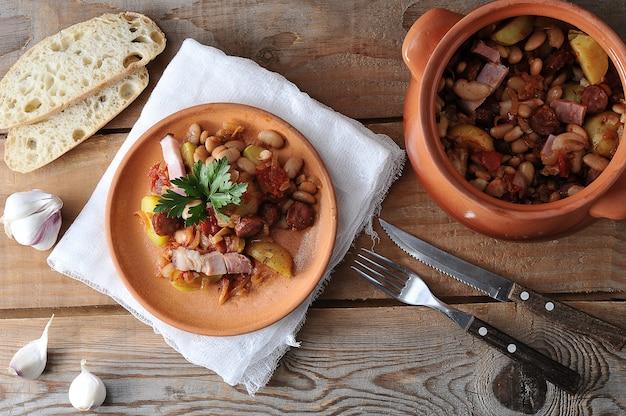 Piatto cotto in una pentola con patate, fagioli, affumicato in una pentola di terracotta