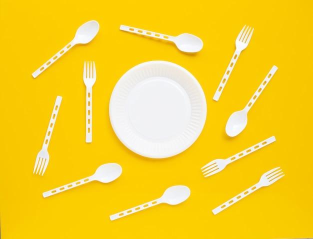 Piatto, cucchiaio e forchetta di plastica su giallo