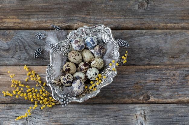 Piatto d'argento con uova di quaglia, piume e mimosa su fondo di legno - priorità bassa di pasqua