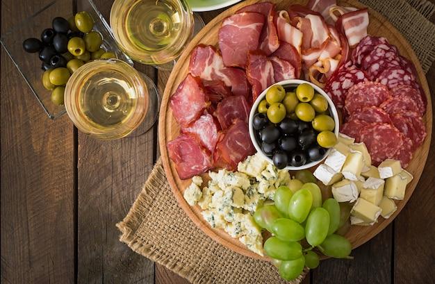 Piatto da antipasto con pancetta, scatti, salame, formaggio e uva