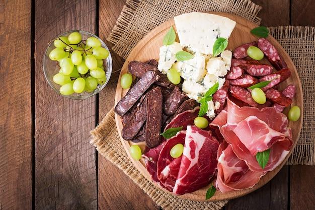 Piatto da antipasto con pancetta, scatti, salsiccia, gorgonzola e uva