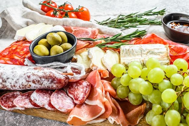 Piatto da antipasto. piatto di carne affumicata a freddo con salsiccia, prosciutto affettato, prosciutto, pancetta, olive. varietà di antipasti. sfondo grigio. vista dall'alto