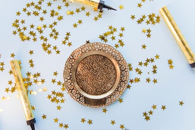 Piatto decorato degnato con stelle incandescente e candele dorate su sfondo blu