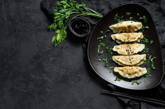 Piatto degli gnocchi giapponesi fritti di gyoza sulla tavola nera rustica.