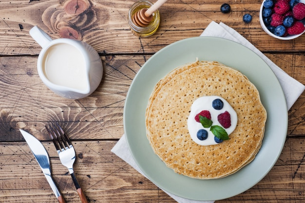 Piatto dei pancake sottili deliziosi con le bacche sulla tavola di legno