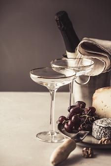 Piatto del formaggio e di champagne su calcestruzzo