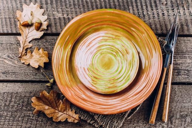 Piatto del pranzo del ringraziamento con forchetta, coltello e foglie su legno