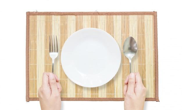 Piatto del primo piano con la forchetta e cucchiaio in mano della donna sulla stuoia isolata su fondo bianco