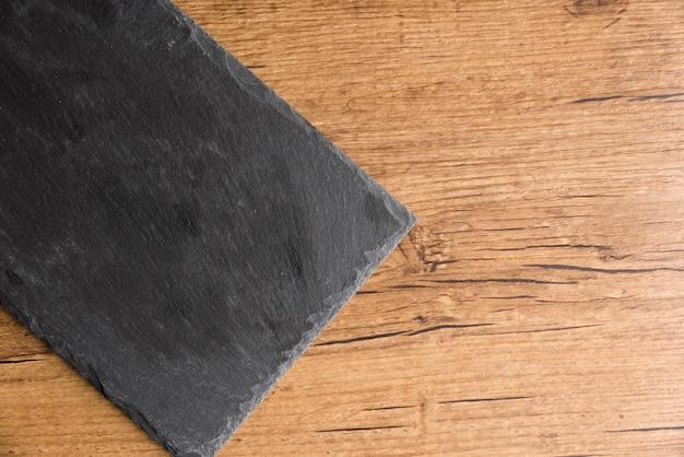 Piatto della lavagna su fondo di legno