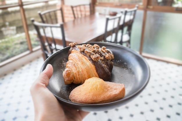 Piatto della tenuta della mano della gente che serve panetteria al forno fresca